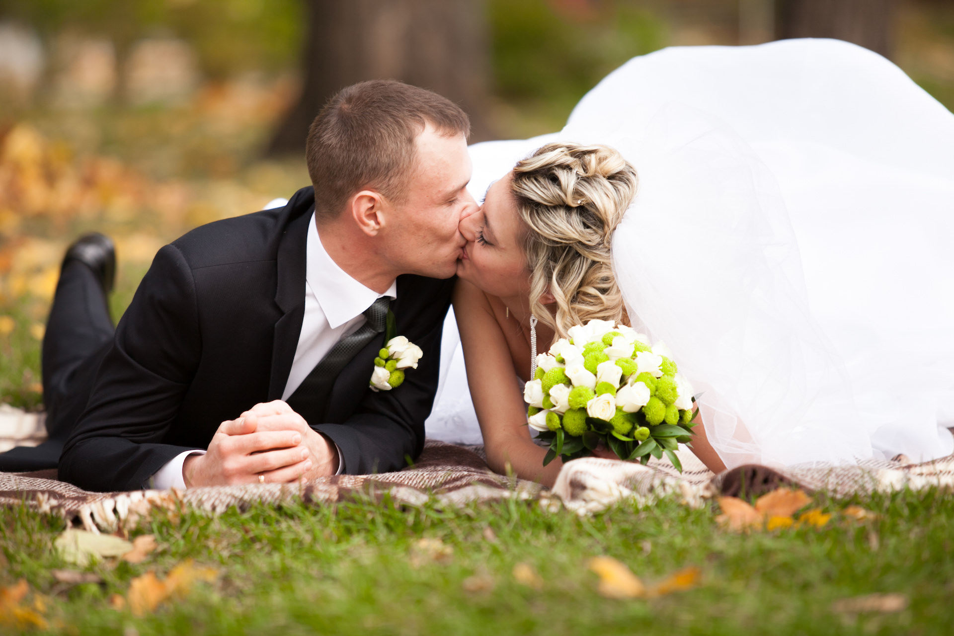 newly married couple lying on grass at park and kissing
